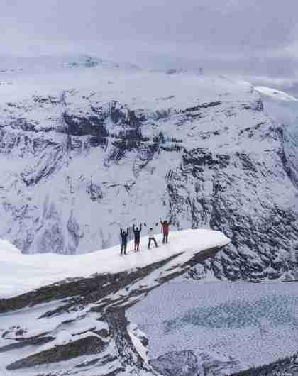 Vier Personen mit Schneeschuhen stehen oben auf der Trolltunga in Fjord Norwegen im Winter