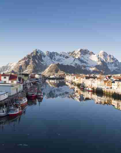 Wooden houses, fishing boats and snowcapped mountains, Henningsvær in certified Sustainable Destination Lofoten, Northern Norway
