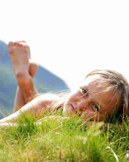 Young girl relaxing in the gras on a sunny summer day