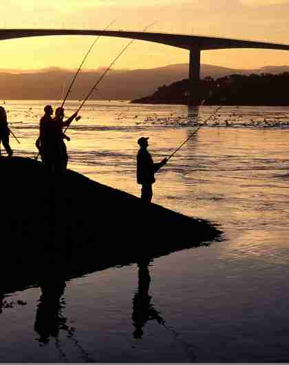 A group of people fishing under the midnight sun in Saltstraumen in Bodø, Northern Norway.