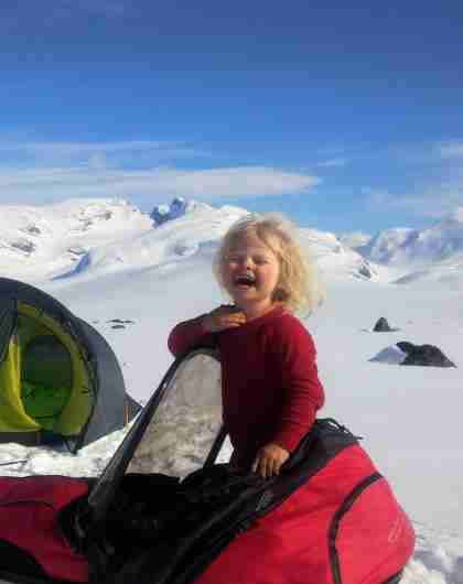 The 4-year-old Mina standing in a ski pulk in front of a tent on a sunny winter day in Jotunheimen national park, Eastern Norway