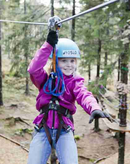 A girl in a zip line in Oslo Sommerpark, Norway