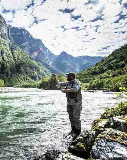 A man fishing for wild salmon in the Nærøydalselva in Fjord Norway