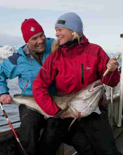 A woman and a man holding a newly caught cod in Lofoten in Northern Norway