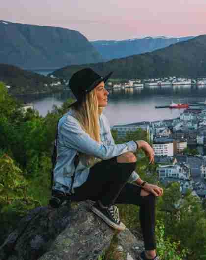 Kortreist byferie: En dame sitter og skuer utover Ålesund fra Aksla utsiktspunkt