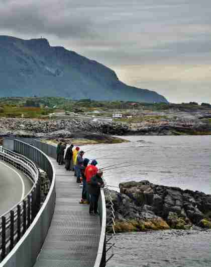 A group of people fishing from the Myrbærholmen fishing bridge on The Atlantic Road in Fjord Norway.