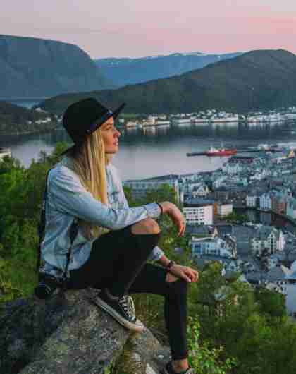 A woman on a city break in Norway is overlooking Ålesund from Aksla viewpoint