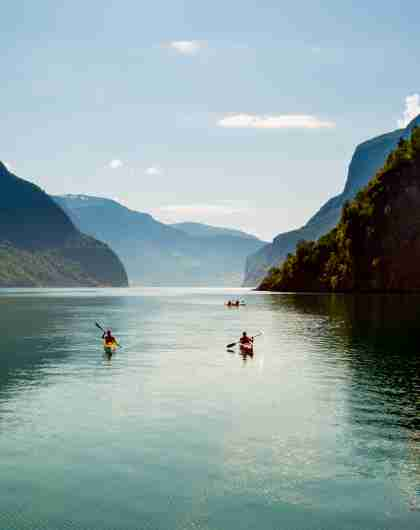 Two people kayaking on the Nærøyfjord surrounded by mountains on a sunny day, Fjord Norway