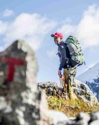 A man hiking past a safety cairn in the mountains