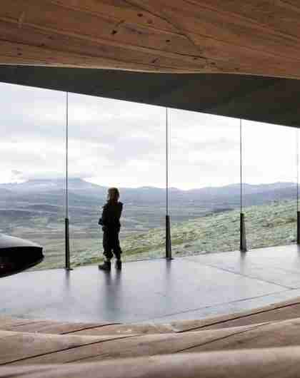 A person looking at the view from inside the Viewpoint Snøhetta in Hjerkinn.
