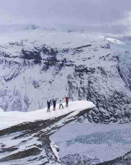 Un grupo de cuatro personas con raquetas de nieve disfruta las vistas desde lo alto de Trolltunga, en la Noruega de los fiordos, en un día de invierno.