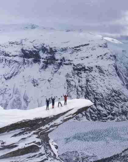 Fire personer med truger på Trolltunga på Vestlandet