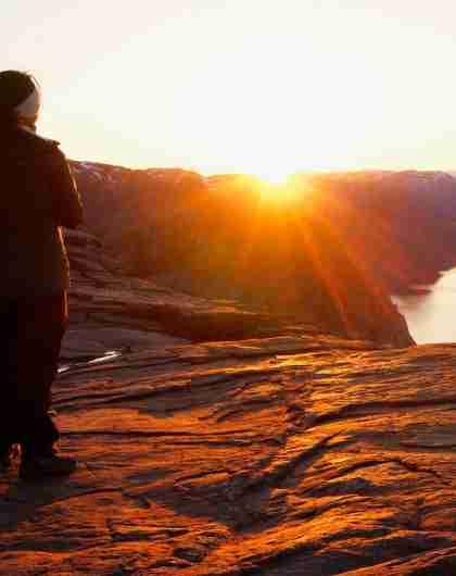 En person ser på soloppgangen fra Preikestolen i Ryfylke i Norge