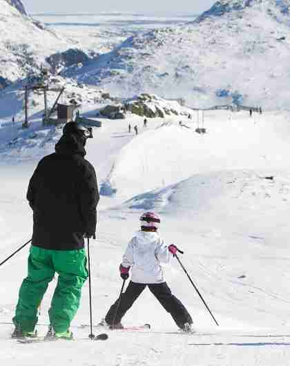 Two adults and two children alpine skiing in Hemsedal, Eastern Norway