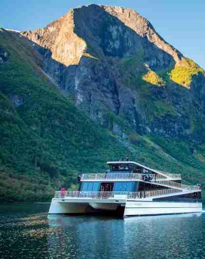 Hybridskipet Vision of the Fjords på Aurlandsfjorden omgitt av høye fjell