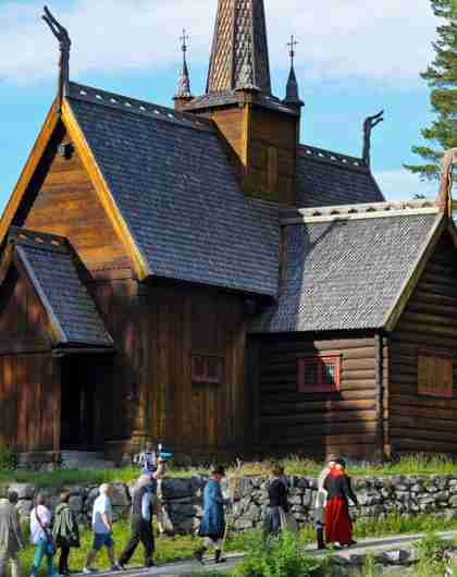 A group of people in old costumes walk past the stave church at Maihaugen in Lillehammer, Eastern Norway
