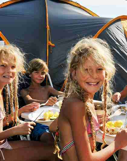 Children eating outside a camping tent on Hamre famliecamping in Kristiansand, Southern Norway