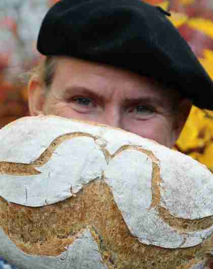 A man is holding up a bread with flour designed as a moustache in Norway