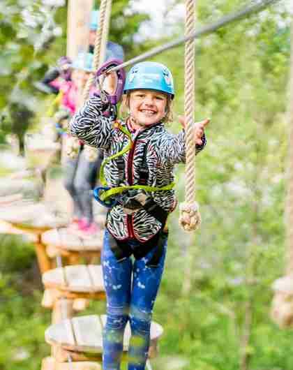 En jente på familieferie i Trysil på Østlandet, i klatreparken Høyt & Lavt