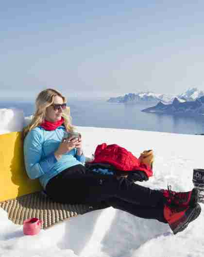 Woman enjoying a break on a winter hike to Mount Ryten in Lofoten, Northern Norway