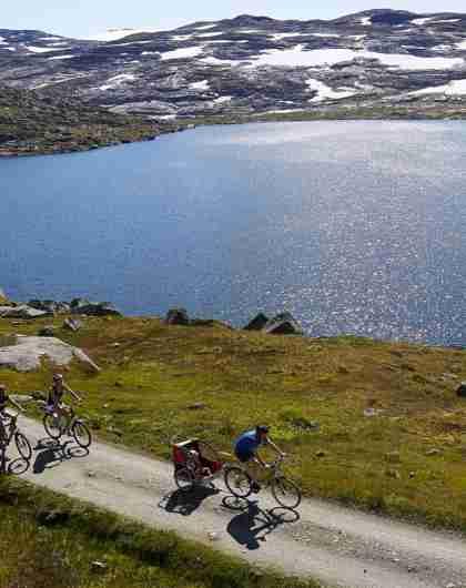 En gruppe cyklister ved en sø langs Rallervegen i det østlige Norge