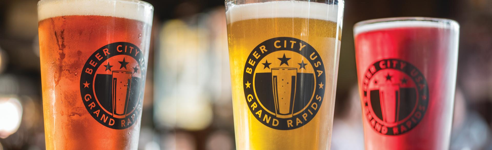 Three pint glasses that read 'Beer City USA Grand Rapids' filled with different beers.