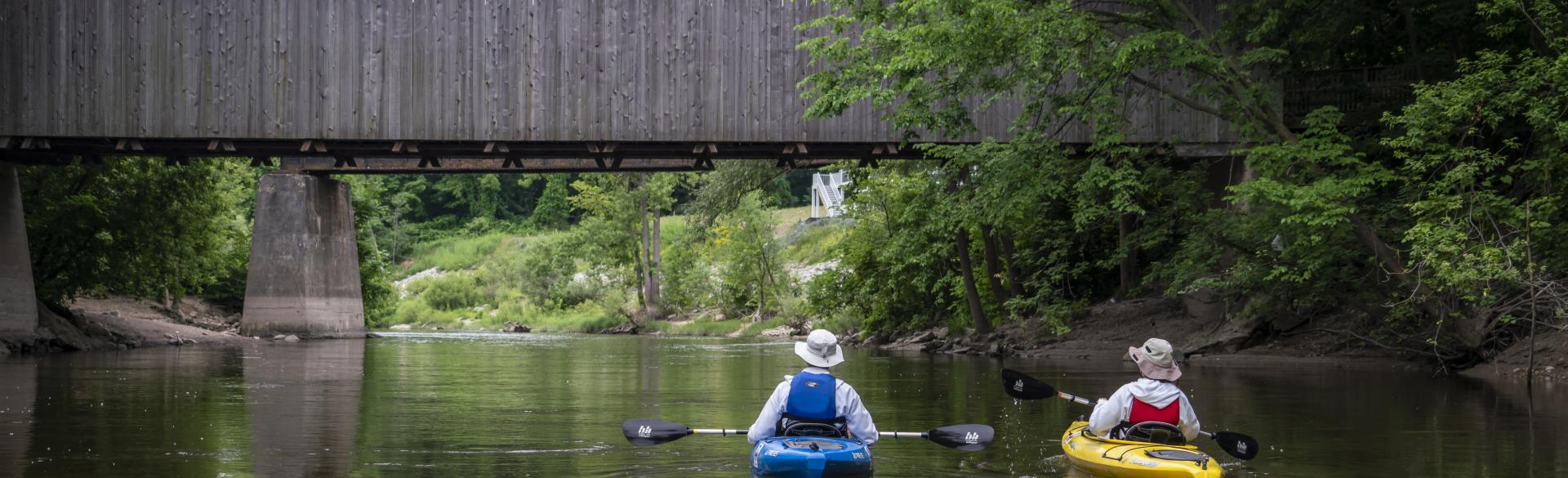 Two people kayaking down the Grand River.