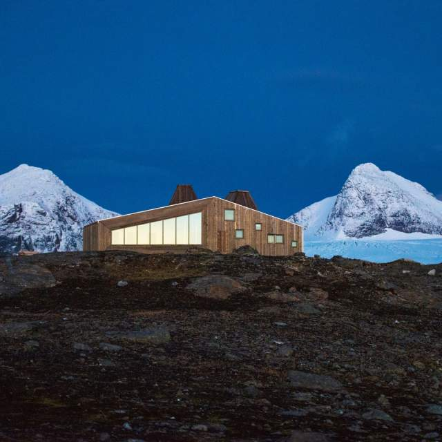 The Rabothytta cabin in Helgeland with snowcapped mountains in the background