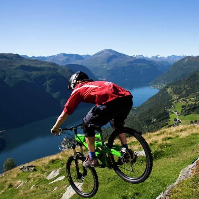 En person sykler ned en åsside mot Storfjorden på Vestlandet