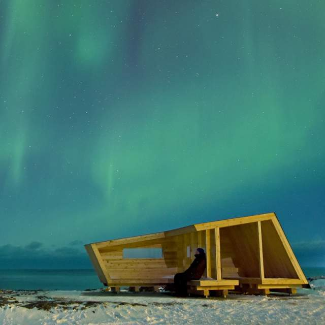 Hasselneset bird hide under the northern lights on the Varanger peninsula, Northern Norway