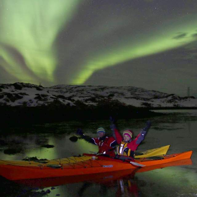 Anita Andresen on a kayak below the Northern Lights close to Tromsø in Northern Norway