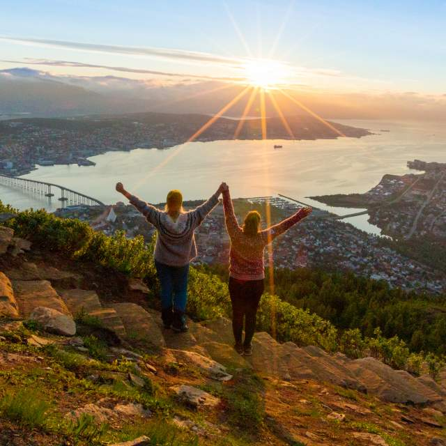 Two women are hiking up the Sherpa staircase to Mount Storsteinen in Tromsø, Northern Norway