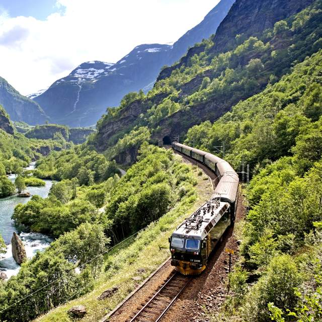 The Flåm railway going through the landscape of green hills and spectacular mountains in Fjord Norway