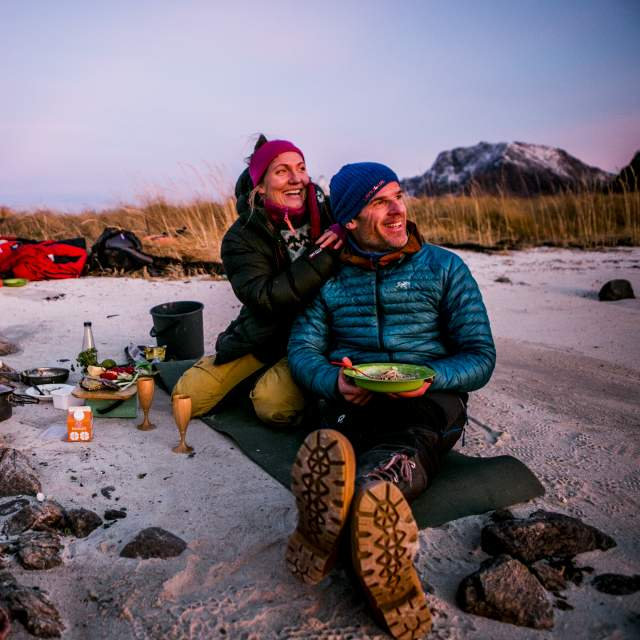 Two campers having a cosy campfire dinner on a beach in the evening light