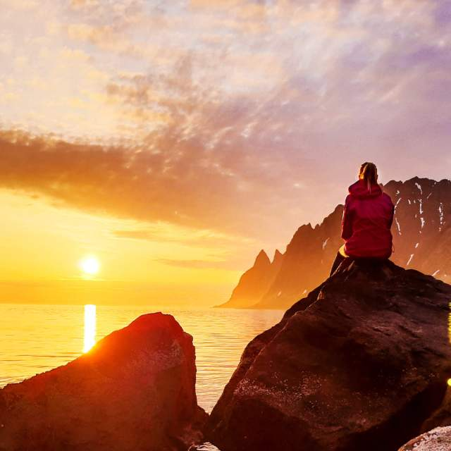 A person watching the midnight sun at Senja in Northern Norway