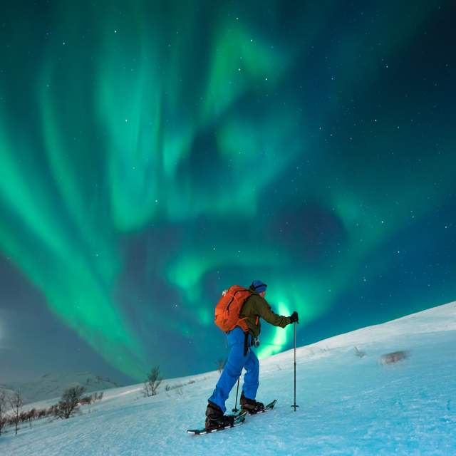 A person snowshoeing under the northern lights in Tromsø, Northern Norway