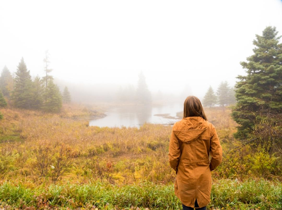 A person in an orange jacket in front of a lake in the fall at Riding Mountain National Park
