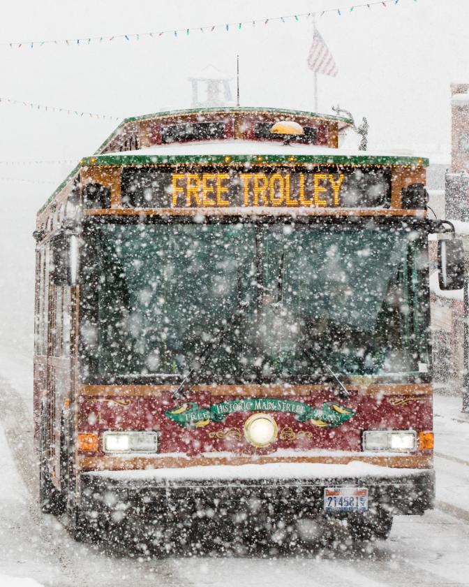 Trolley Driving Down Snowy Main Street