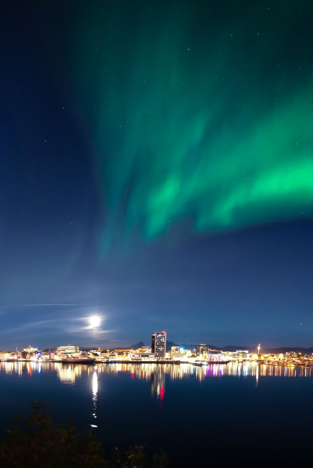 The northern lights dancing across the sky above the city of Bodø, Northern Norway