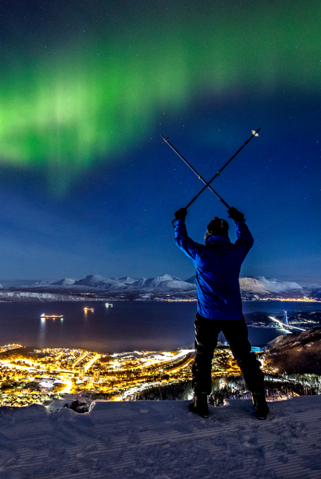 A man alpine skiing over Narvik town while spectacular northern lights