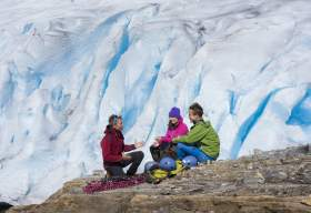 Three people sitting on a rock near the Svartisen glacier, Northern Norway