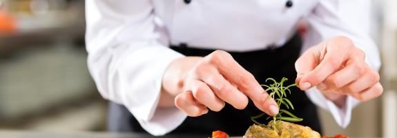 Chef preparing a plate with garnish