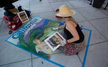 Artist creating a sidewalk chalk picture of a rural scene