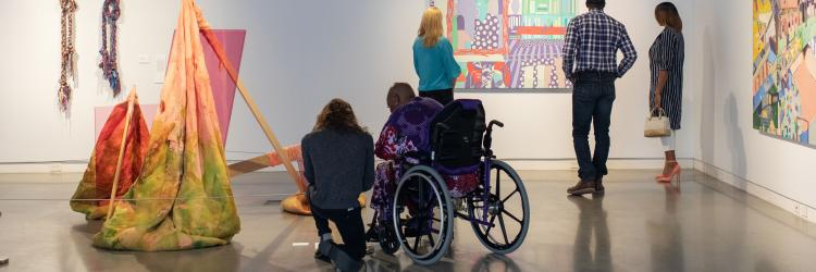 Group exploring art at UICA, one visitor in a wheelchair.