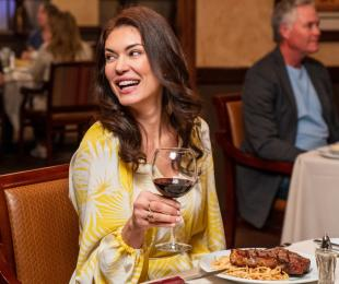 Woman Drinking Wine at Dinner