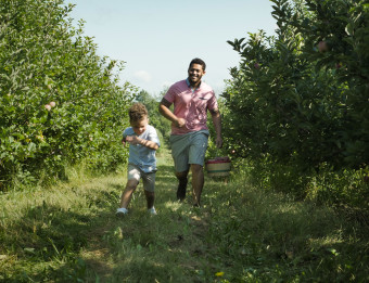 Father and son running through orchard in Kent County.