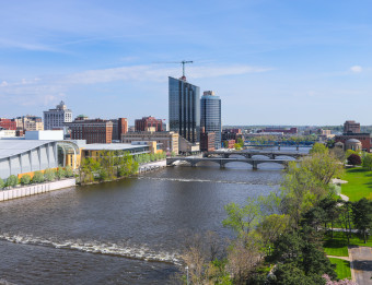 Skyline: 2019. Showcases convention center and downtown hotels off of the Grand River. Developments on the Amway Grand Plaza Hotel roof.