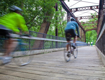 Two People Speeding Across a Bridge on Bikes