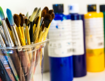 A cup of paintbrushes with bottles of paint in the background