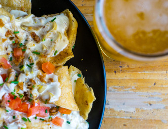 A plate of Brewery Vivant's duck nachos and a pint of beer.